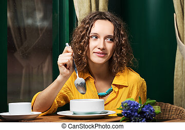 Happy young woman eating a soup at restaurant