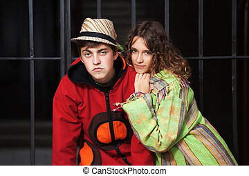Young hippie couple against an iron fence