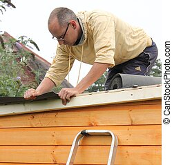 Building a wooden shed and laying the felt on the roof to...
