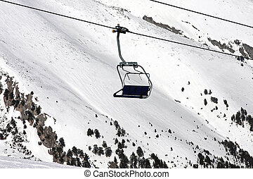 Chairlift - Four seat chair lift in snowy mountain