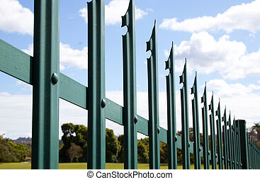 Closeup of green steel palisade security fence against blue...