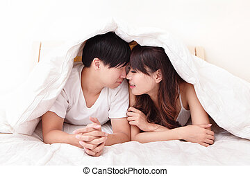 young lovely couple lying in a bed, happy smile face, asian...