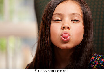 Little girl sticking her tongue out - Playful little girl...