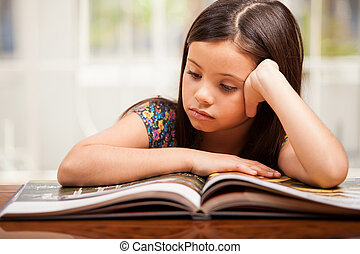 Little girl focused on reading - Portrait of a pretty little...