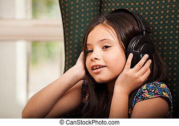 Little girl listening to music - Pretty little Hispanic girl...