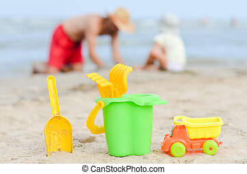 Father and son playng on sandy beach toys closer to viewer