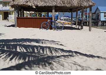 Blue bike on the Sand - A blue bicycle leans against a post...