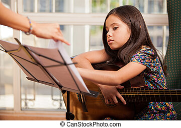Taking guitar lessons - Cute little girl playing the guitar...