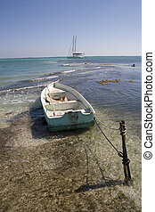 Small wooden boat and stake - A small wooden boat is tied to...