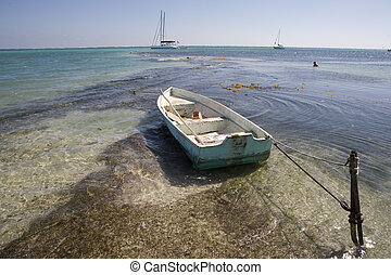 A small wooden boat is tied to a stake - A small wooden boat...