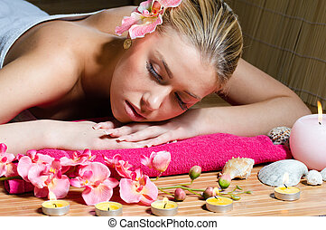 Beautiful woman relaxing during massage with flowers,...