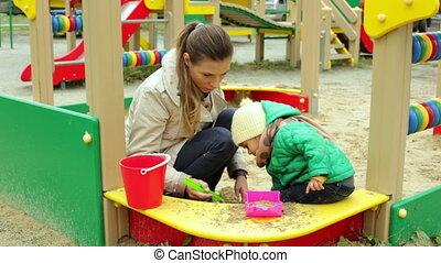 Sandpie - Mother and daughter making a sandpie together
