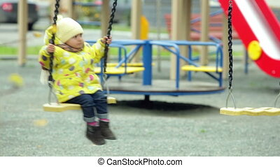 Playground fun - Charming kid having fun swinging on the...