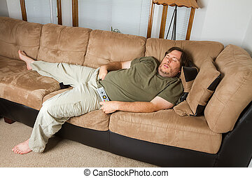 Man asleep on the couch - Fat man sleeping on the couch with...