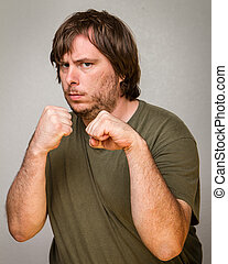 Fist up and ready to brawl - A guy ready to fight with his...