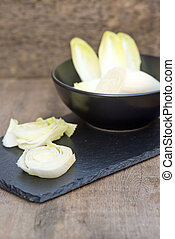 Fresh chicory witloof heads in rustic setting with wooden backgr