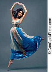 beautiful girl floating in mid-air, blue silk dress