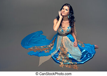 beautiful Indian girl in a blue dress sitting on the floor