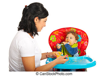 Mother giving puree to her baby boy and having conversation...