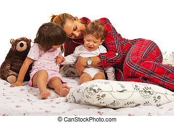 Mother playing with her kids in bed