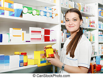 Pharmacist holding out tablets in bottle at drugstore -...