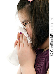 Runny Nose - Closeup view of a young girl blowing her nose,...