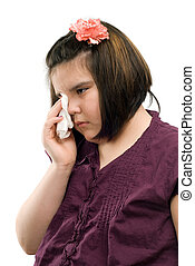 Sad Child - A sad girl is wiping her eyes with a tissue,...