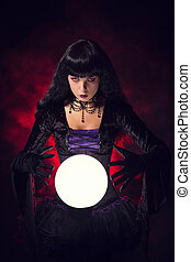 Beautiful witch or fortune teller with a crystal ball,...