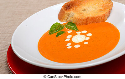 Delicious bowl of tomato soup with grilled bread and basil -...