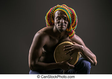 tom-tom player - Rastafarian african american man playing...
