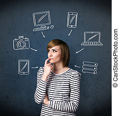 Young woman thinking with drawn gadgets around her head -...