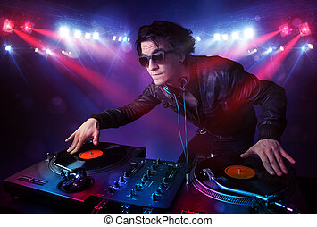 Teenager dj mixing records in front of a crowd on stage -...