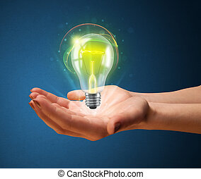 Glowing lightbulb in the hand of a woman