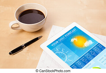 Workplace with tablet pc showing weather forecast and a cup...