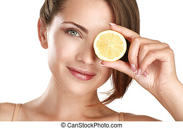 Woman beauty concept with fruits slices over eyes on white