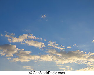 Blue sky with clouds lit by the sunset