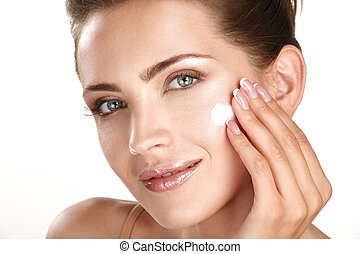 beautiful model applying cosmetic cream treatmen on her face...