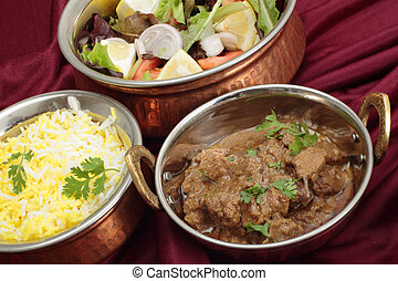 Rogan josh rice and salad bowls - Indian copper dishes with...
