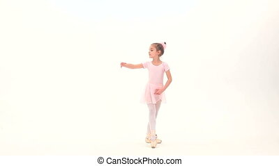 Little ballerina posing in a studio