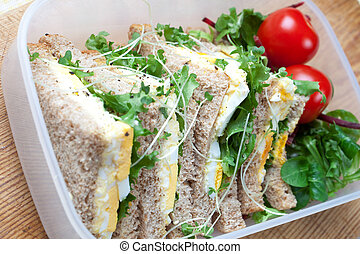 Healthy egg sandwich for lunch with tomatoes in a lunch box