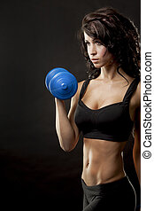 fitness woman - fitness model brunette holding weights on...