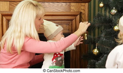 Christmas tree decorations - Mother decorating Christmas...
