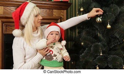 On Christmas Eve - Mother decorating Christmas tree with her...