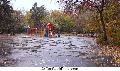 Children's playground in the fall. It's snowing,...