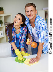 Couple at home - Young couple cleaning table surface with...