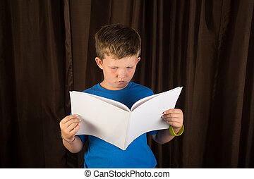 Young Boy Reading Blank Book or Magazine - A young boy...