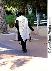 A religious Jew in the praying traditional robe walking down...