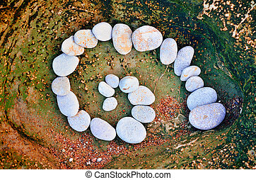 Stone Volute - Spiral of pebbles on the sea boulder