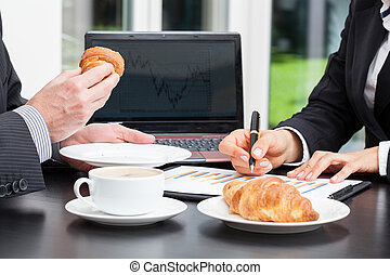 Business people with coffee and croissant during chart...