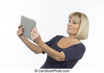 Senior woman using a tablet computer photographed in studio...